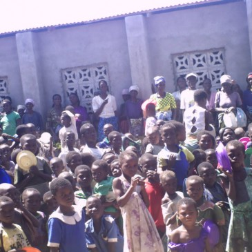 Orphans and elderly be side the hall we have constructed for their feeding program.